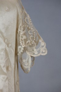 Image: Sleeve detail from Wedding dress, jacket, and slip. Cream linen and taffeta with crocheted lace, 1910. 90.19.42a-c