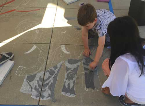 Young visitor drawing with chalk